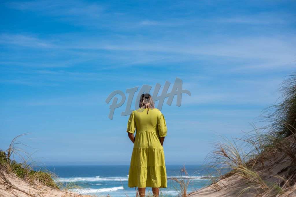 Rear view of woman standing on cliff and looking at ocean