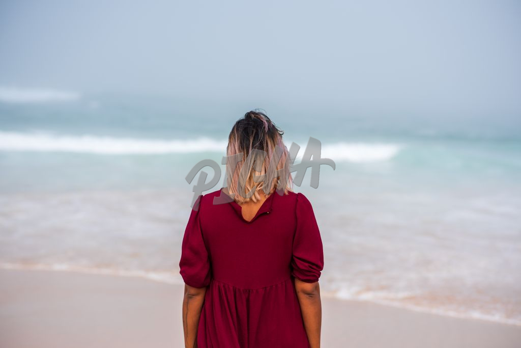Woman standing on coastline and looking at ocean