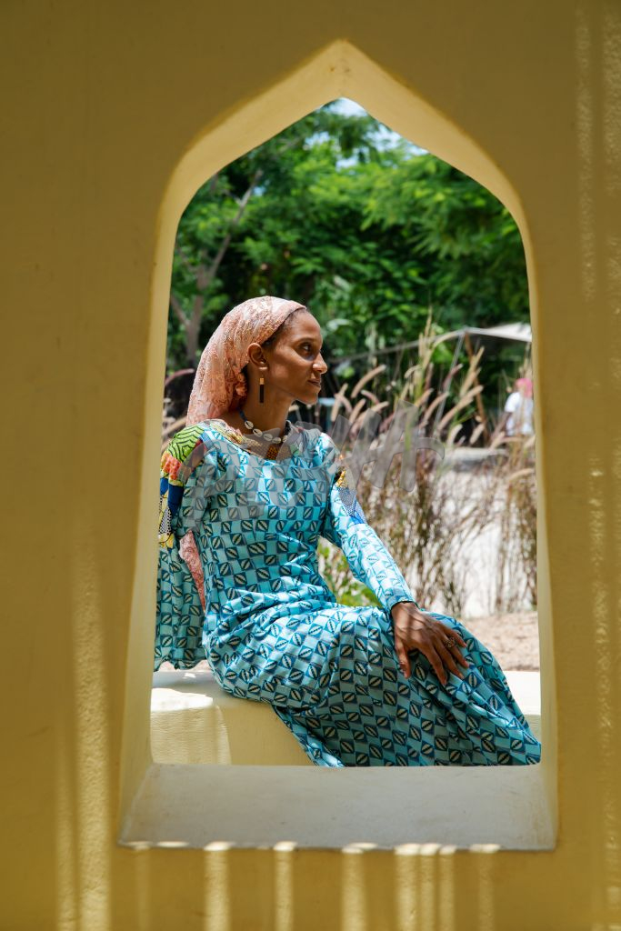 Woman framed by window sits out in the sun