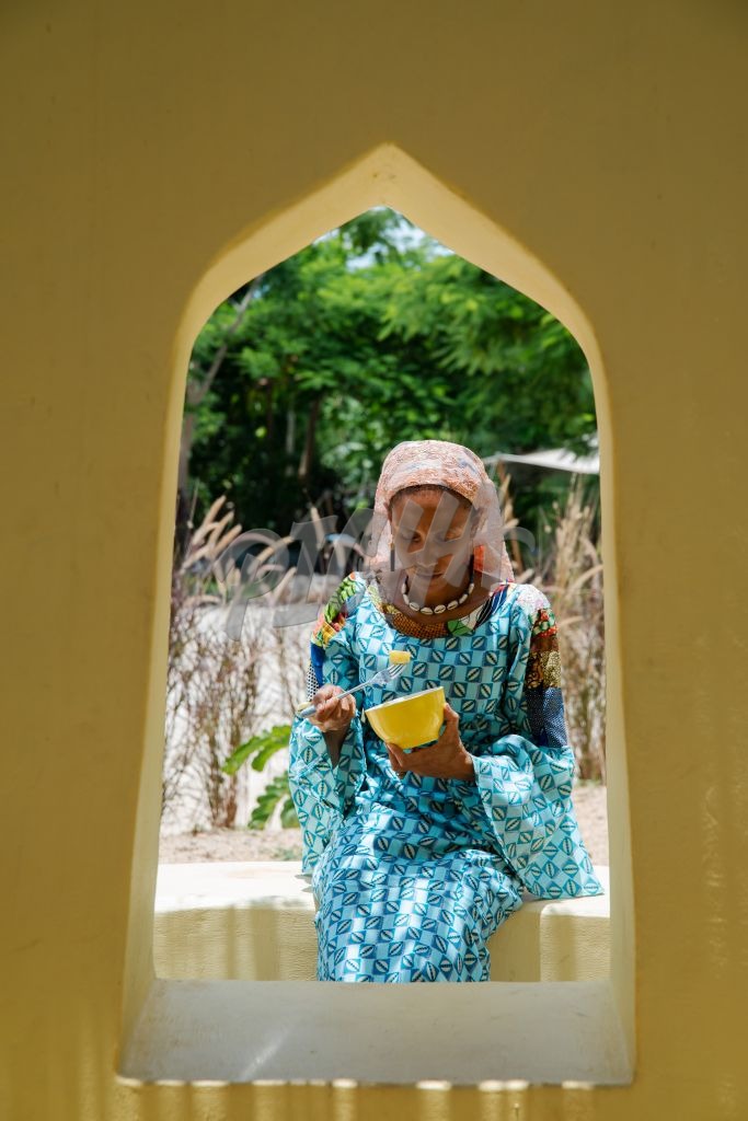 Woman eating fruit from a yellow bowl