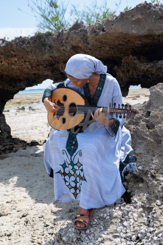 Woman playing Oud by the ocean