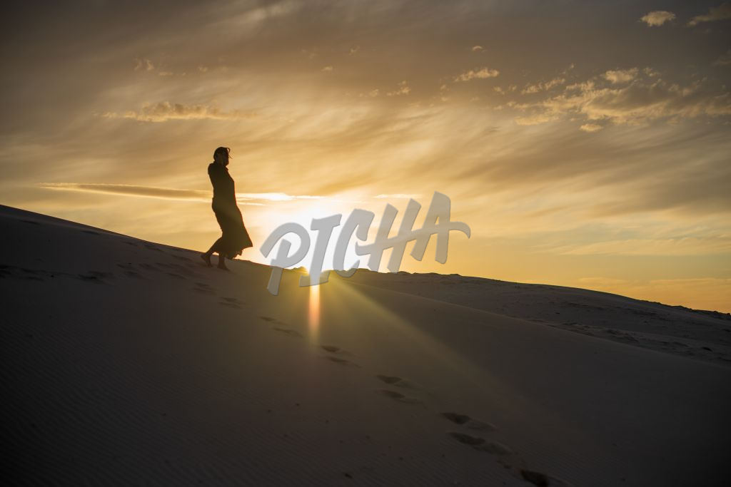 Silhouette of woman walking on sand dune