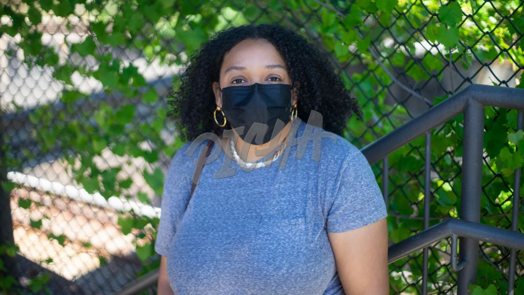 women with curly hair wearing a mask outdoor