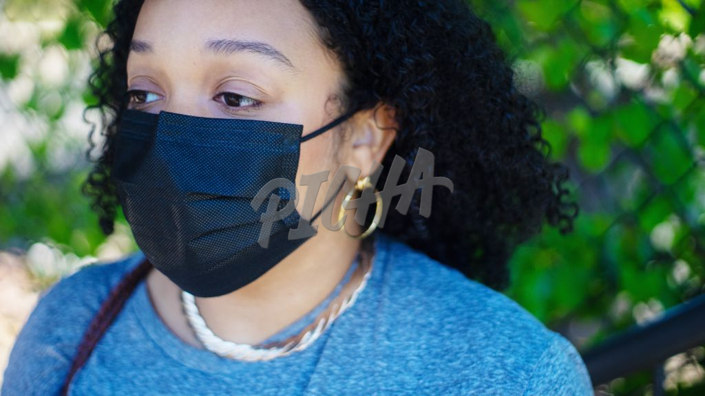 Woman with curly hair wearing a mask