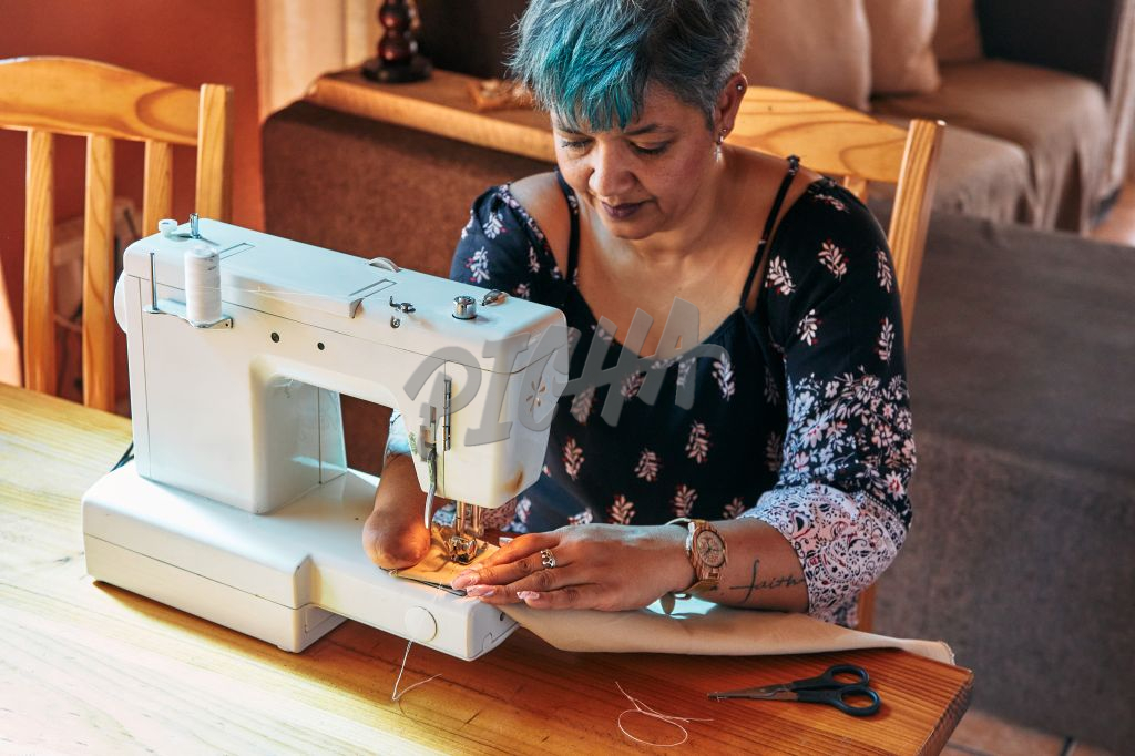 Woman with one hand working on a sewing machine