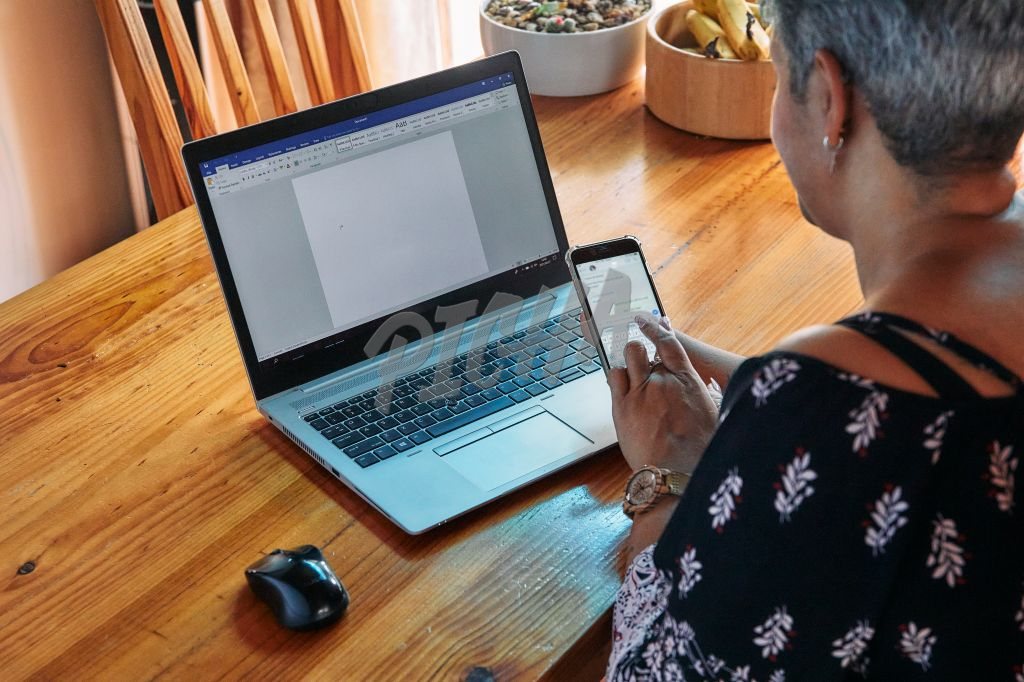 Business woman with one hand working from home on a cell phone