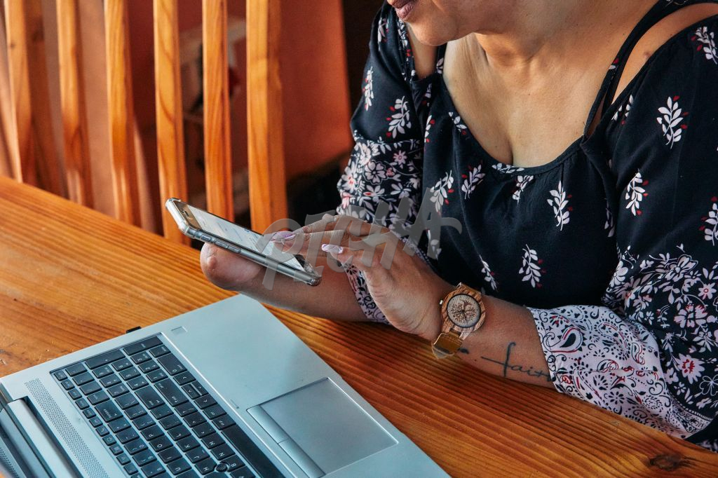 woman with one hand working from home on a cell phone