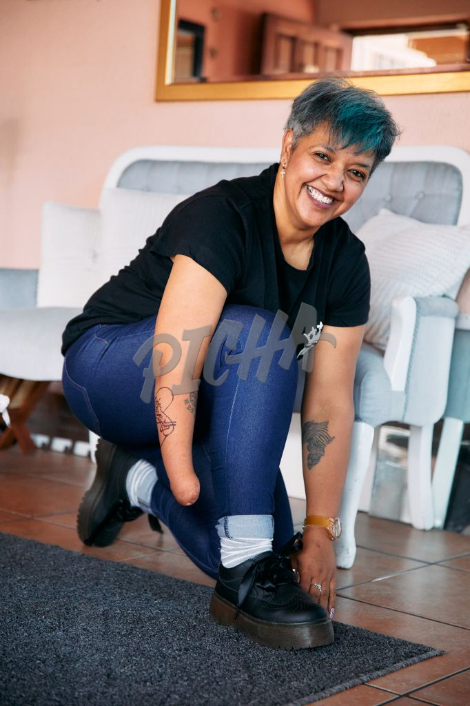 Woman with one arm tying shoe laces happily