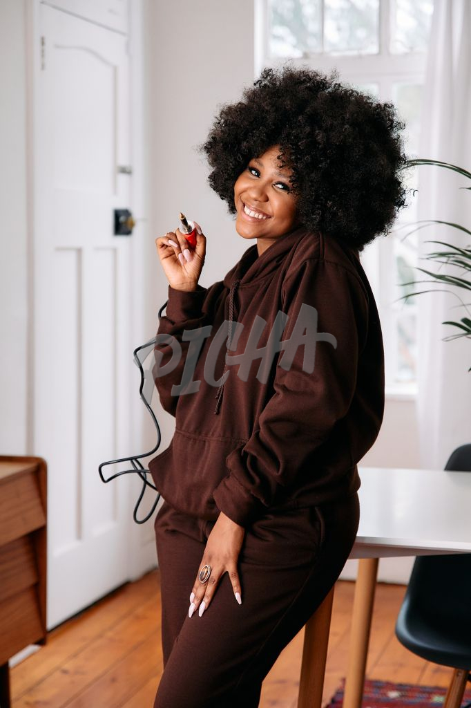 Portrait of a happy woman artist with an afro holding a soldering iron while smiling
