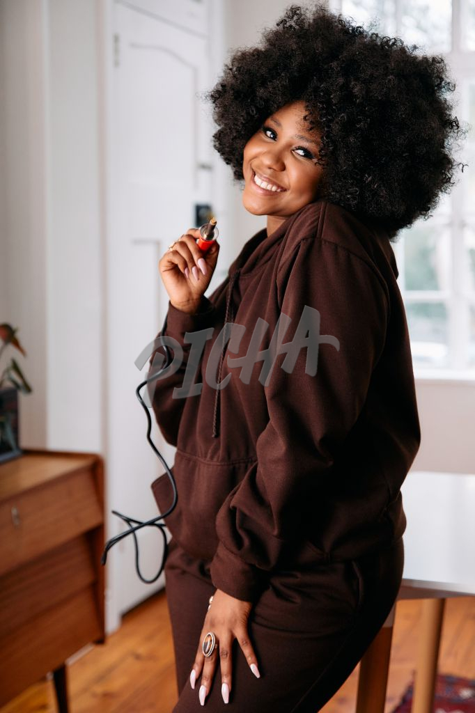Portrait of a happy woman artist with an afro holding a soldering iron enjoying her day