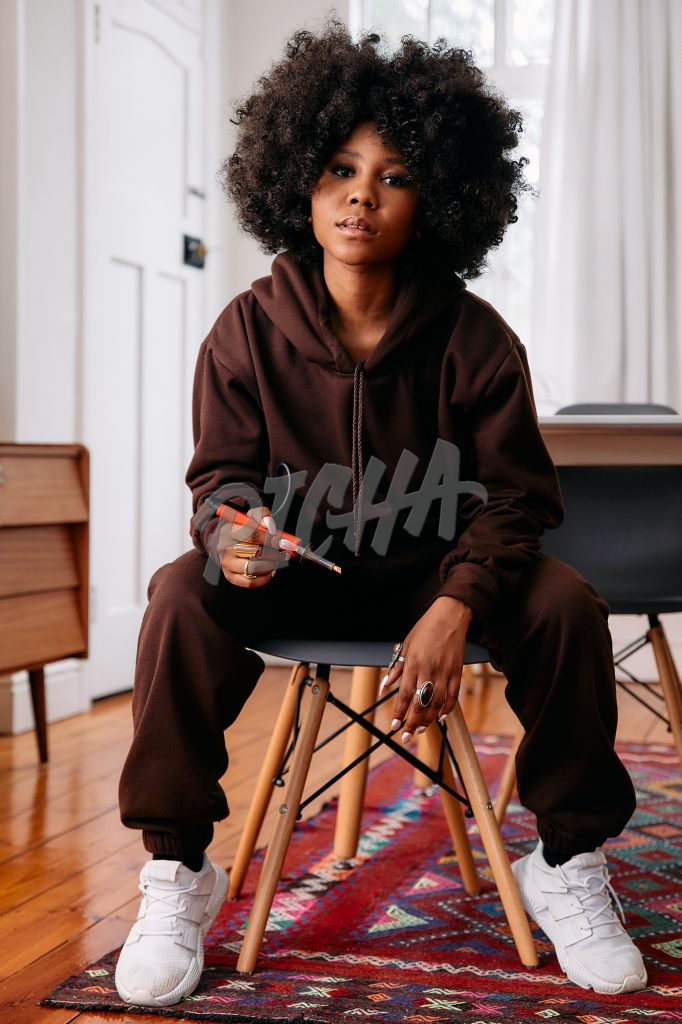 Portrait of a female artist with an afro holding a soldering iron