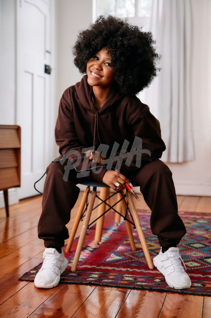 Portrait of a happy woman artist with an afro holding a soldering iron