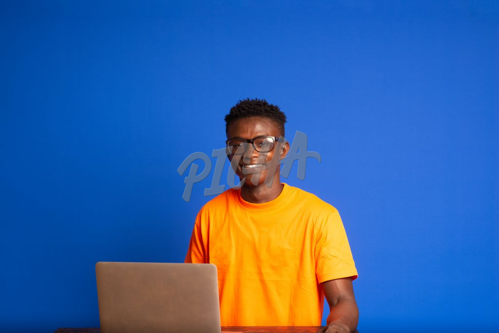 Young man with eye glasses sitting in front of laptop