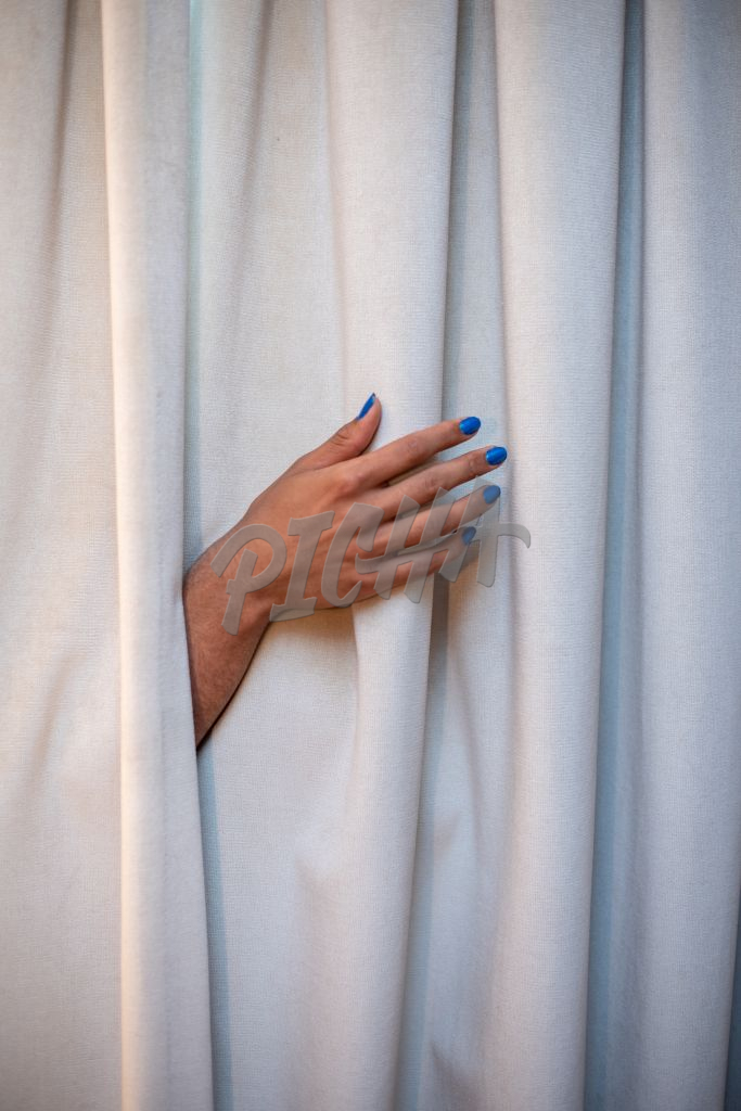 Vertical shot of queer persons hand sticking out of curtain