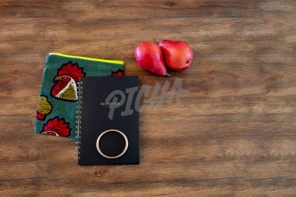 Flat-lay of apples and notebook on desk