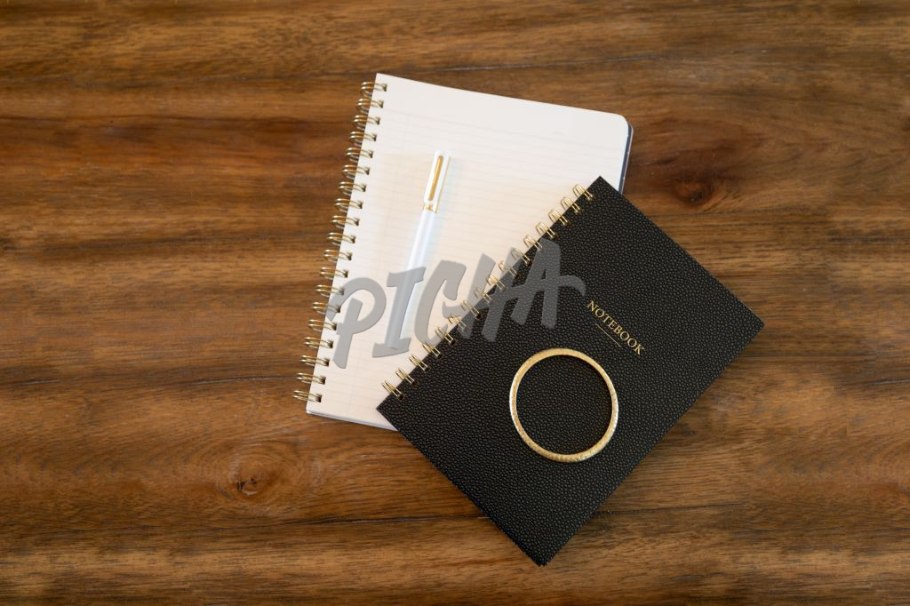 Flat lay of two notebooks and a pen