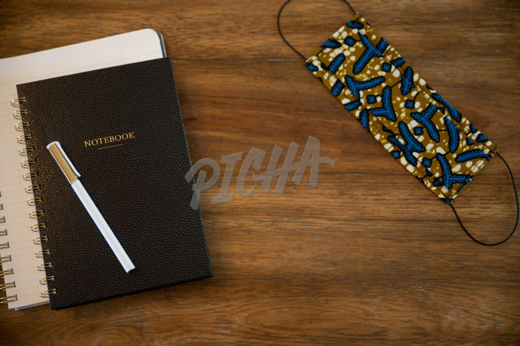 Kitenge face mask next to a pen and notebook