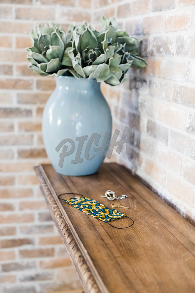 Blue vase with flowers sits at the edge of a console table