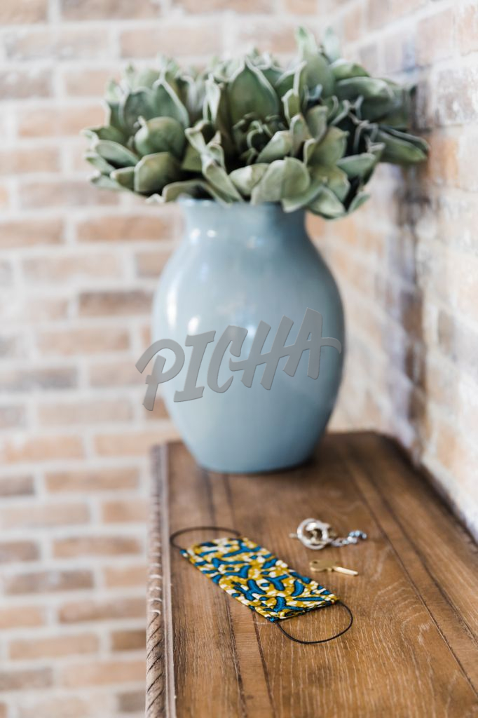 Mask sit beside a blue vase on a console table