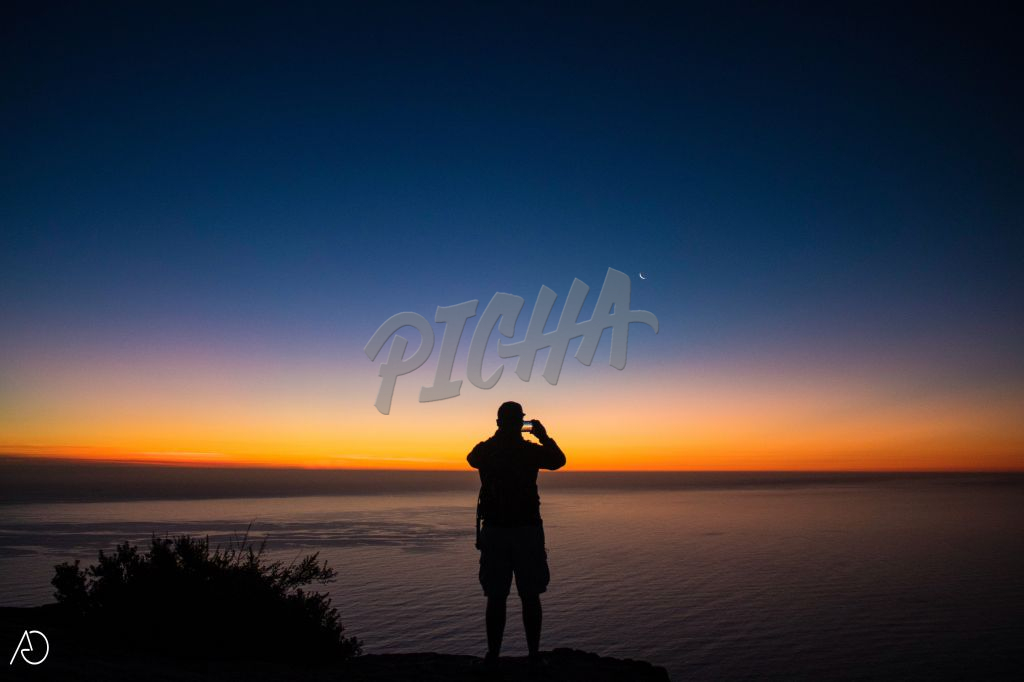A hiker photographs the sunset from atop Lion's Head