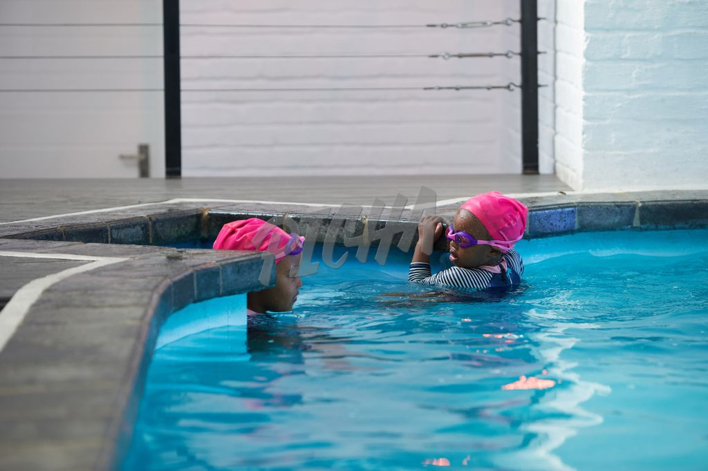 two young girls swimming at the pool
