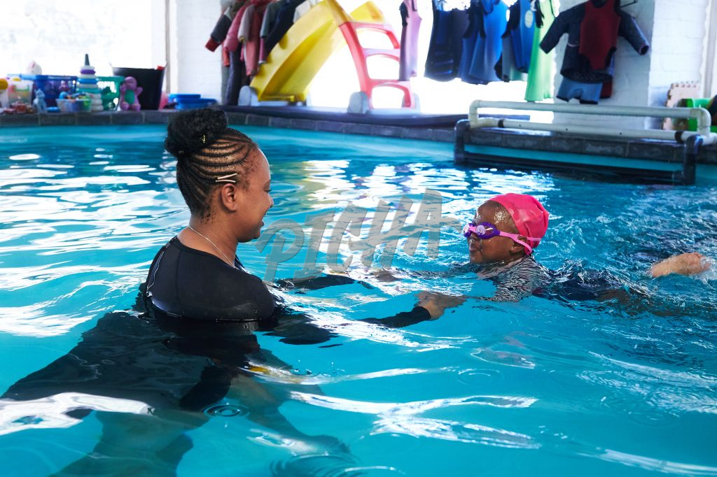 Young girl gets swimming training