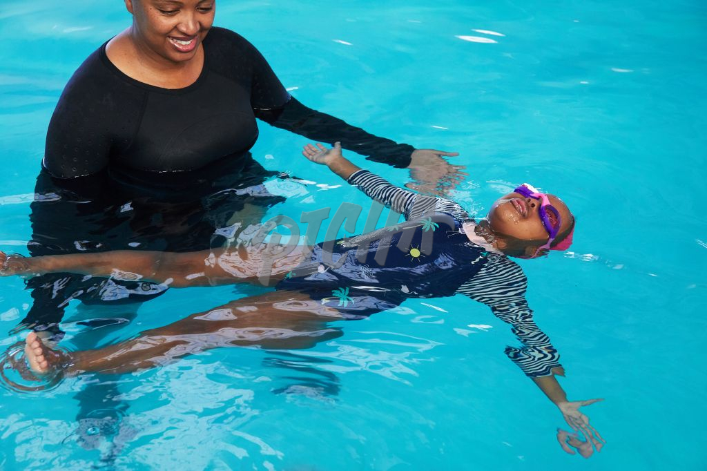 Young girl learns how to float on her back