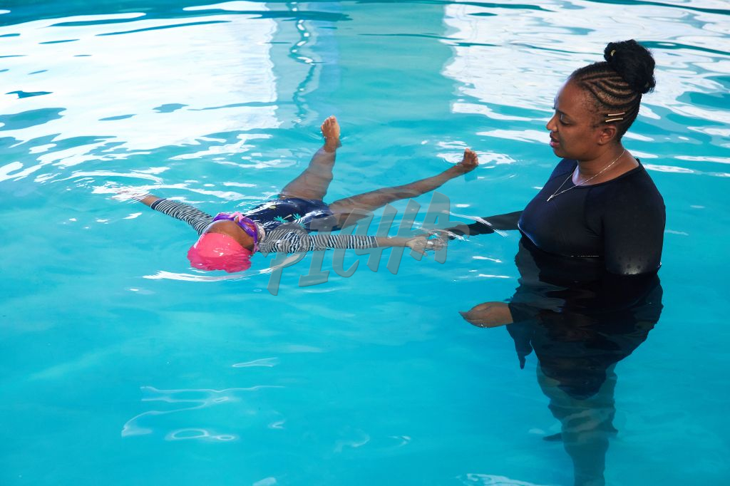 Woman helps young girl practice the survival float