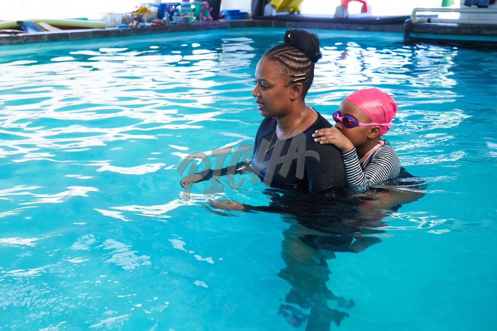 Young girl piggy backs on trainer in the pool