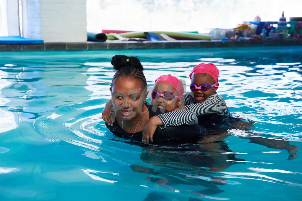 Woman takes  two young girls on piggyback in pool