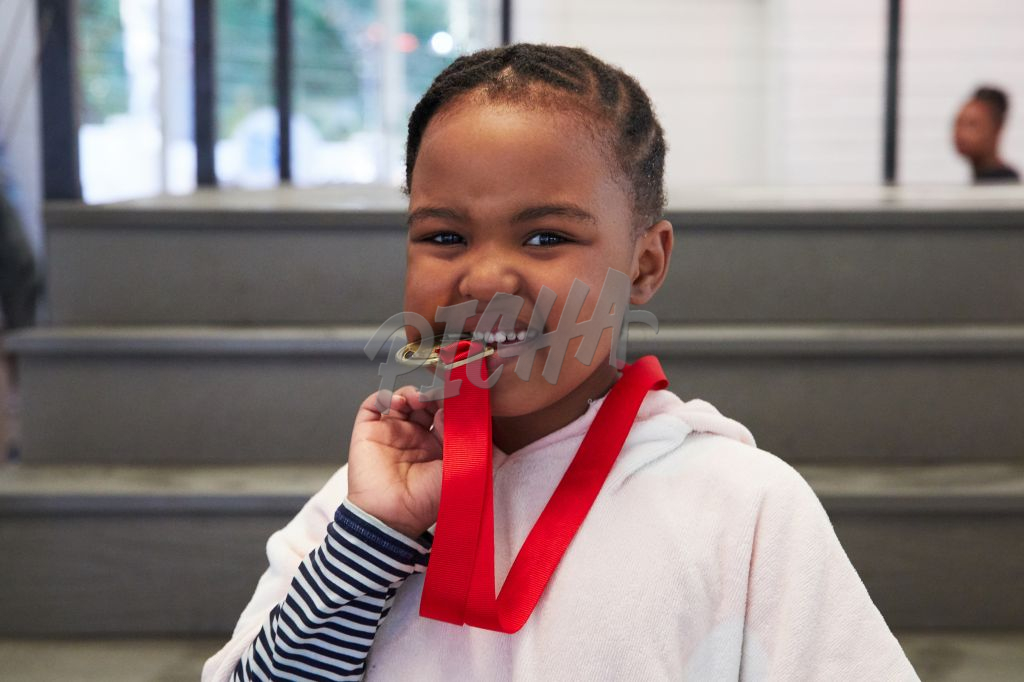 Young girl bites on a medal
