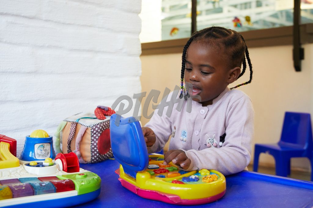 Young girl pushes the buttons on a colourful toy