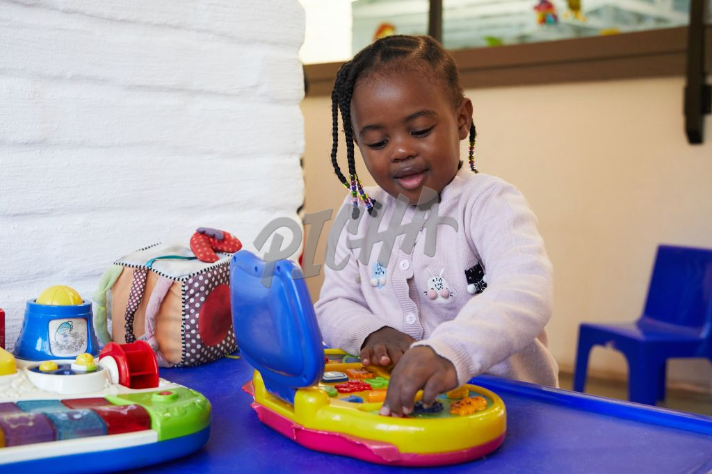 Young girl playing with a colourful toy