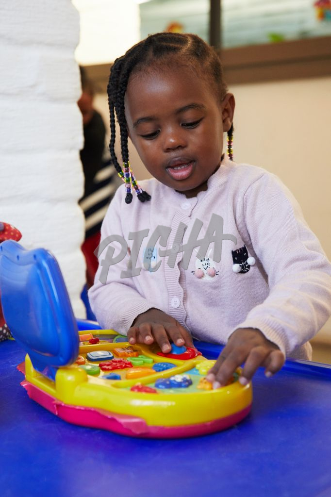Young girl plays with a colourful toy