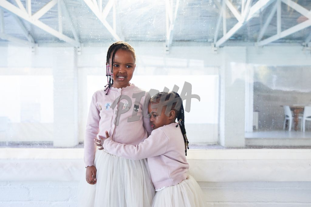 Young girl fearfully clutching onto older sibling