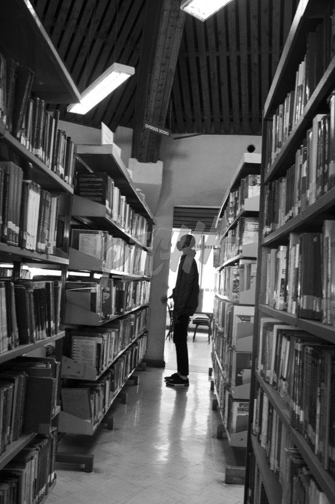Young man standing in the library