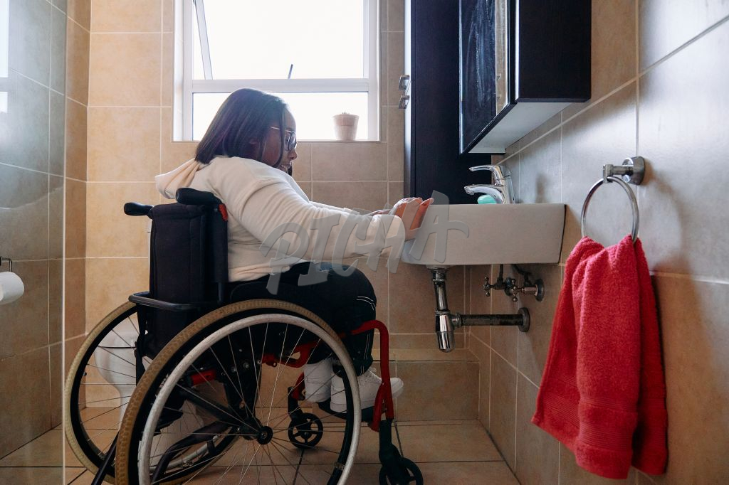 Young Woman in wheelchair doing chores at home