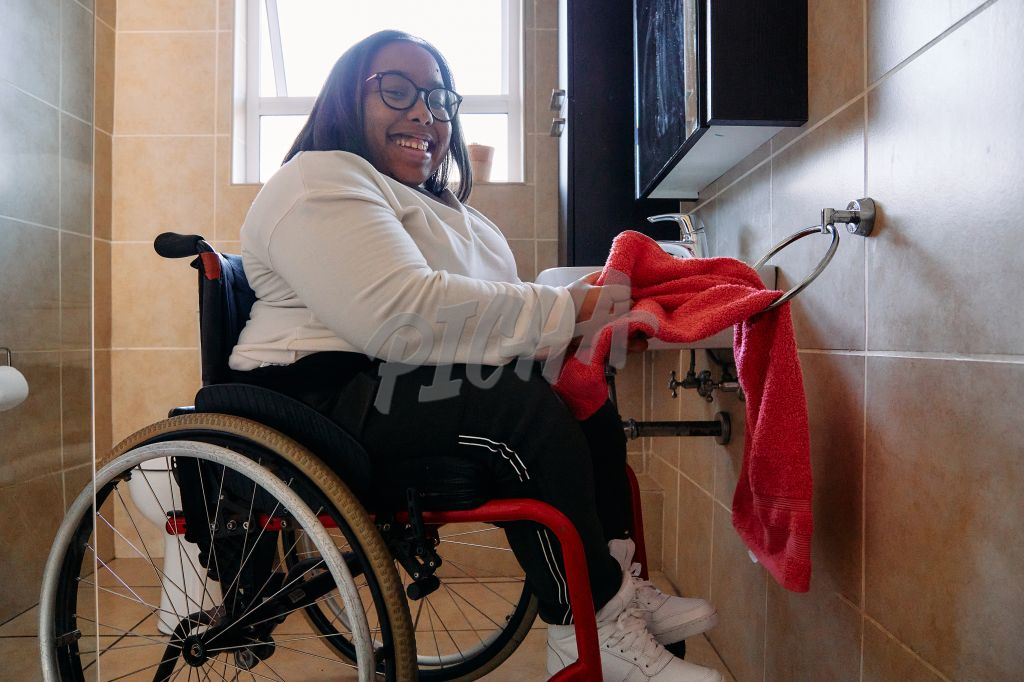 woman in wheelchair drying her hands on a towel