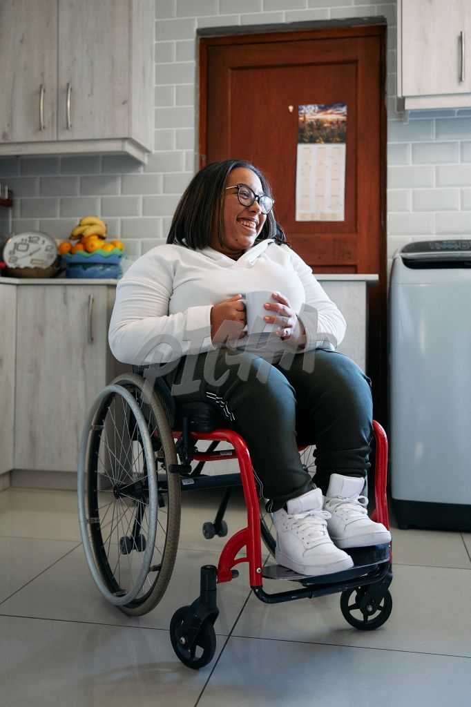 Young Woman in wheelchair smiling in her kitchen
