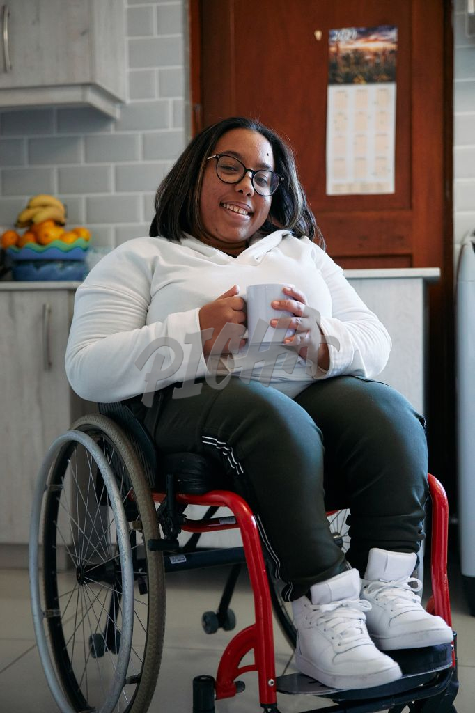 woman in wheelchair having a cup of coffee