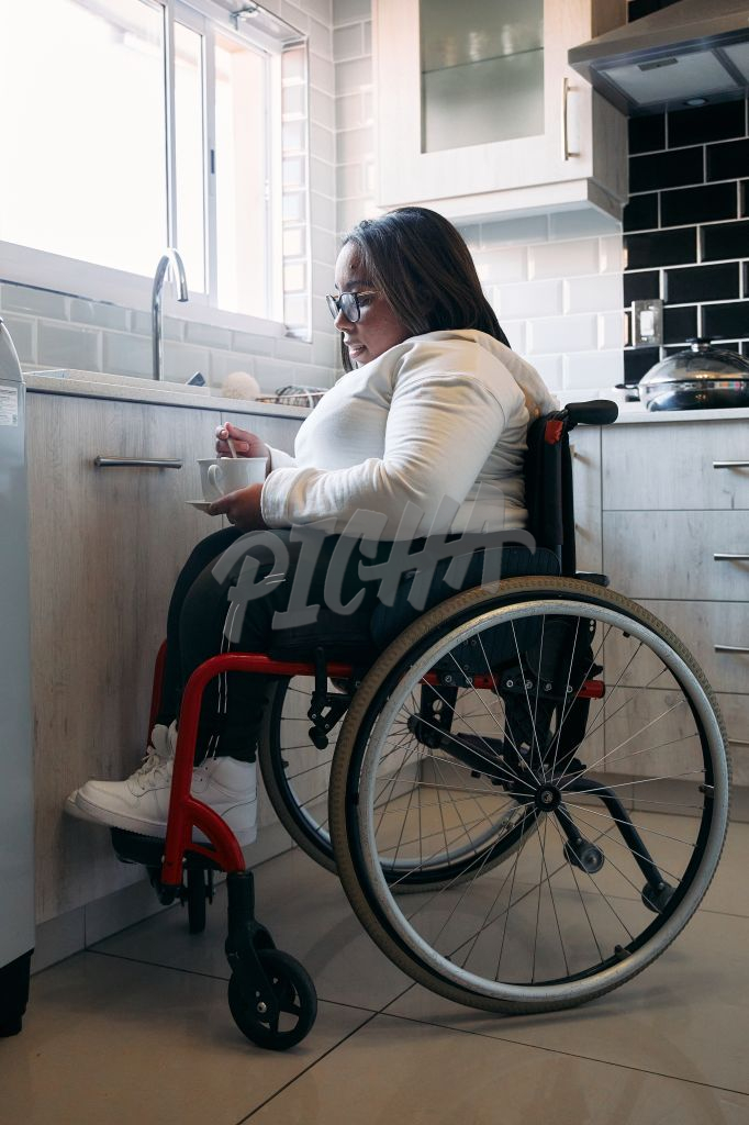 Young woman in wheelchair in the kitchen