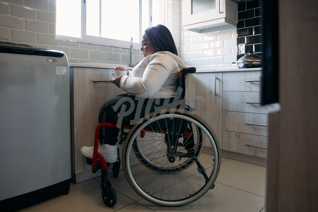 Woman in wheelchair making tea at home