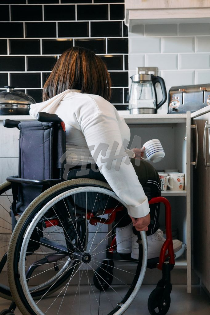 Young woman on a wheelchair getting a cup