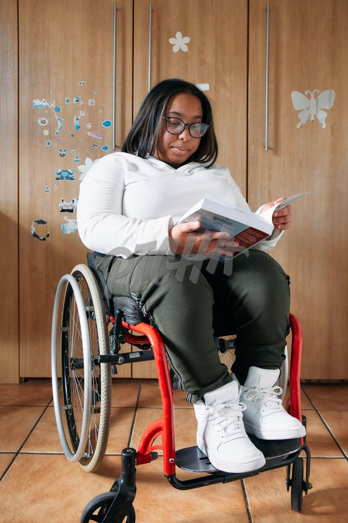 Young Woman with a disability reading a new book