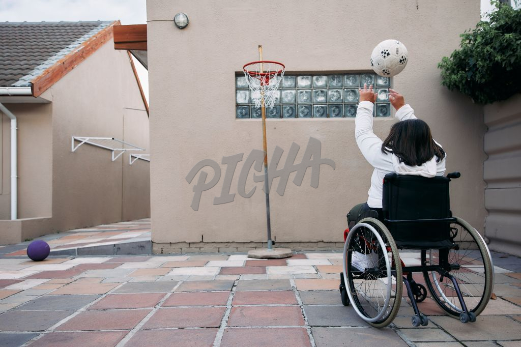 Young Woman with a disability shooting a basket