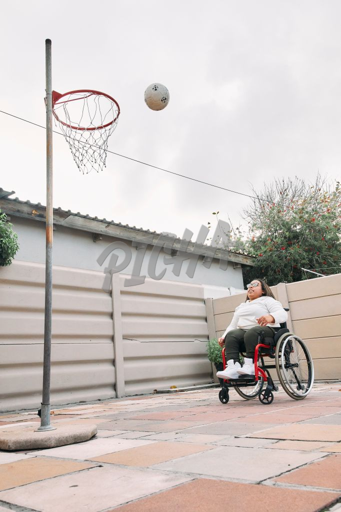 Young Woman with a disability shooting basketballs