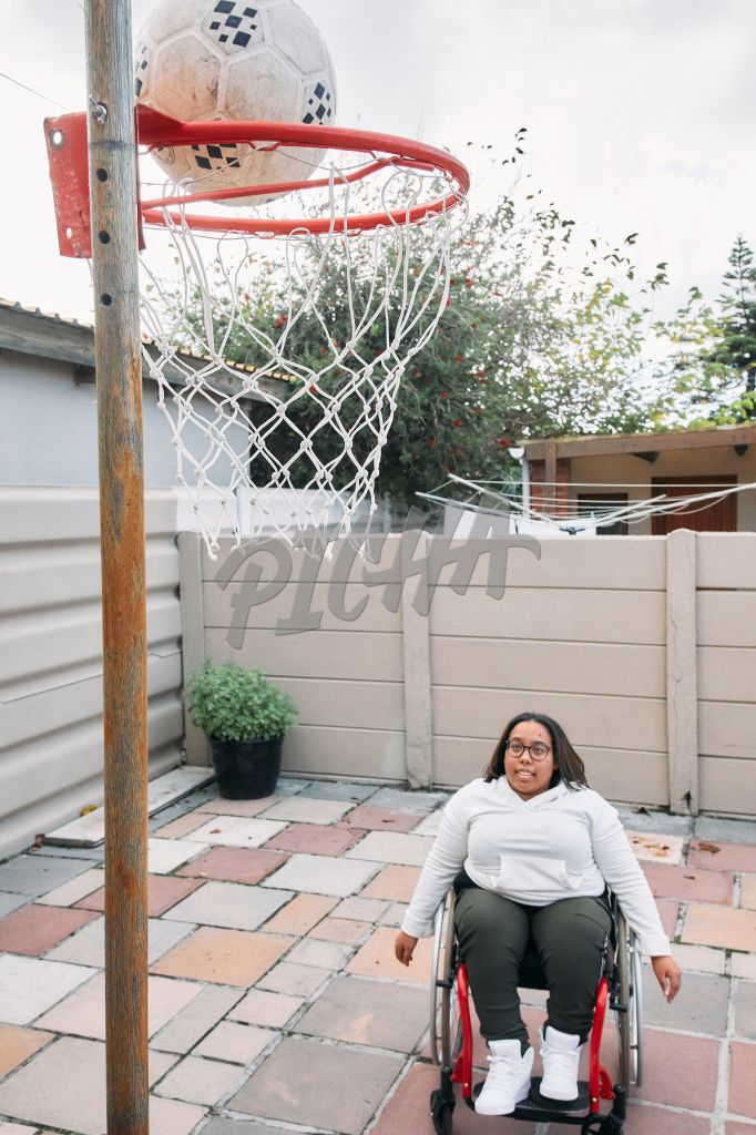 Young Woman with a disability looking at a basketball hoop