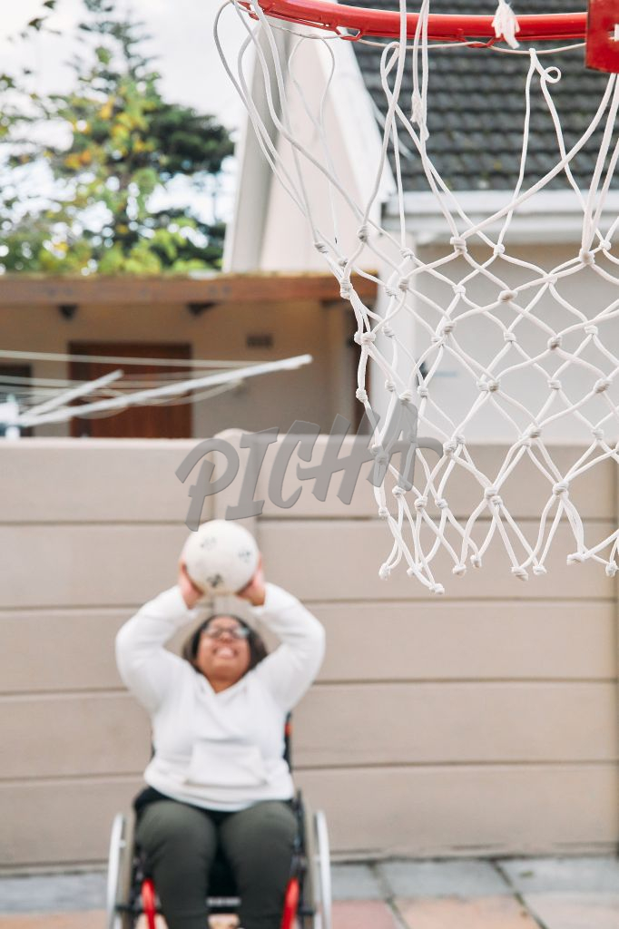 Young Woman with a disability shooting a ball into a basket