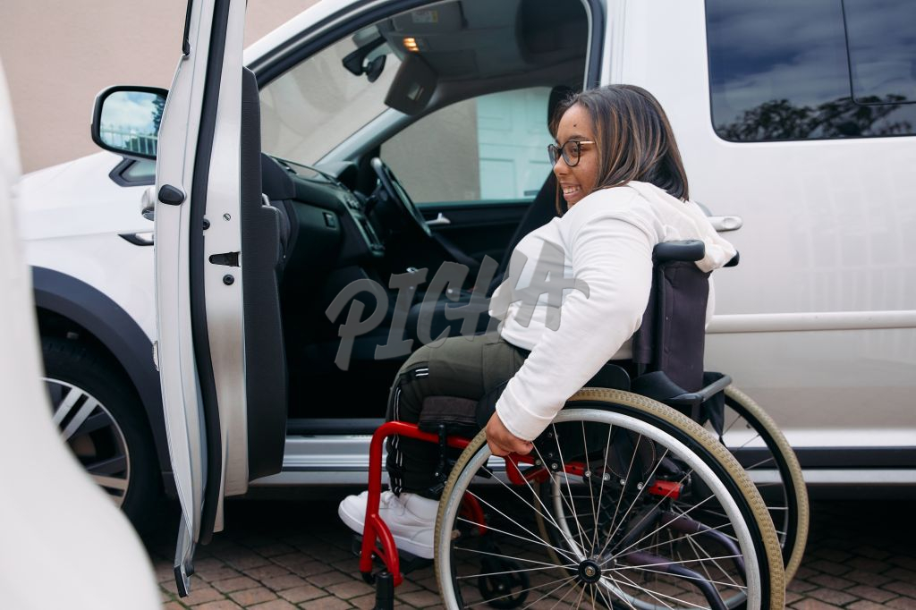 Young Woman with a disability going into a car