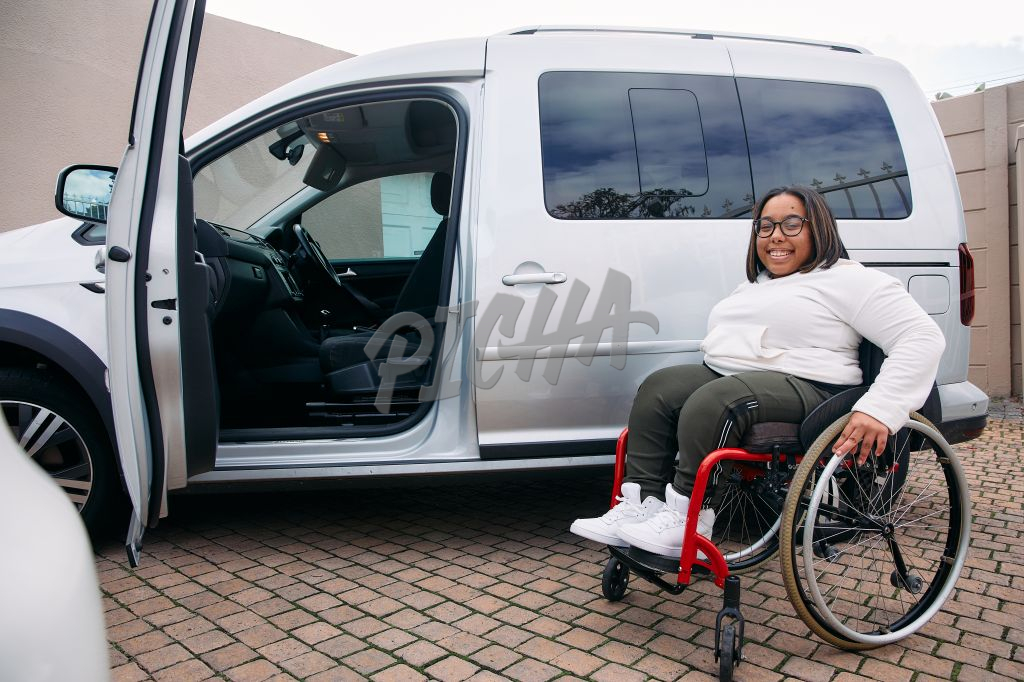 Young Woman with a disability smiling next to her car